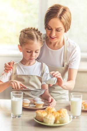 Schöne Frau und ihre niedliche kleine Tochter in Schürzen lächeln, während Muffins mit Zucker Pulver Bestäuben photo