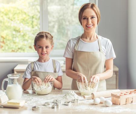 Nettes kleines Mädchen und ihre schöne Mutter in Schürzen suchen in die Kamera und lächelt, während er den Teig in der Küche kneten photo