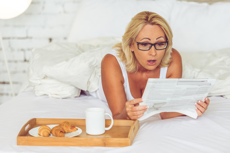 fact: Beautiful middle aged woman in eyeglasses is reading a newspaper and showing surprise while having a breakfast in her bed at home
