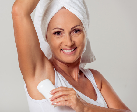 Portrait of beautiful middle aged woman with a towel on her head using a deodorant, looking at camera and smiling, on a gray background