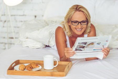 Beautiful middle aged woman in eyeglasses is reading a newspaper and smiling while having a breakfast in her bed at home Stock Photo