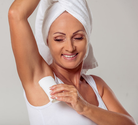 Portrait of beautiful middle aged woman with a towel on her head using a deodorant and smiling, on a gray background