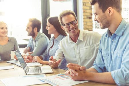 스마트 캐주얼웨어를 사용하는 사업가들은 회의에 참여하면서 가젯을 사용하고 웃고있는 일에 대해 토론하고 있습니다. 스톡 콘텐츠