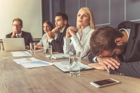 공식적인 착용에 비즈니스 사람들이 회의에 참여하고있다, 전경에서 남자는 그의 손에 기대어있다 스톡 콘텐츠
