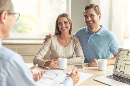 Handsome middle aged realtor in classic shirt and eyeglasses and happy young couple are discussing new house. Couple is drinking coffee and smiling while sitting in office