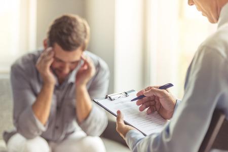 Stattliche deprimierter Mann in Freizeitkleidung lehnt sich auf seine Knie und über seine Probleme zu erzählen, während bei dem Psychotherapeuten auf der Couch sitzen. Doktor im Fokus Standard-Bild - 63378961