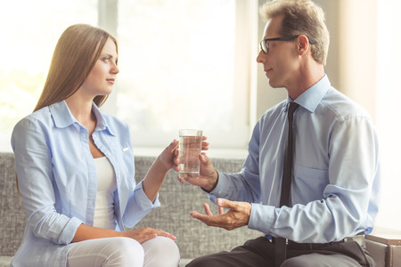 doctor giving glass: Beautiful young woman in casual clothes is sitting on the couch at the psychotherapist. Handsome middle aged doctor is talking to the woman and giving her a glass of water