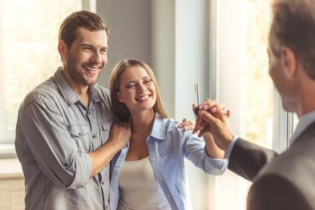 agent immobilier Handsome en costume classique donne la clé du nouvel appartement à heureux jeune couple