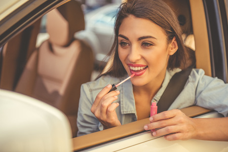 gloss: Nice stylish girl is using a lip gloss and smiling while driving the car Stock Photo