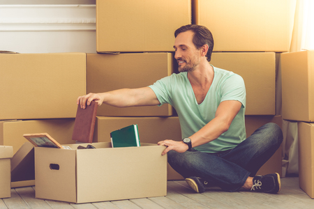 unpack: Handsome mature bearded man in casual clothes is sitting on the floor, packing his stuff into boxes and smiling while moving to the new apartment Stock Photo