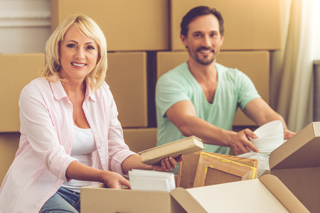 unpack: Beautiful mature couple in casual clothes is packing their stuff, looking at camera and smiling while sitting on the floor among boxes, moving to the new apartment Stock Photo