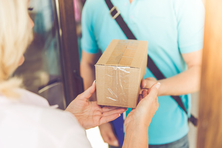 Cropped image of beautiful mature woman getting the delivery from handsome worker while moving to the new apartment Stock Photo