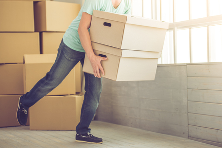 Cropped image of handsome mature bearded man in casual clothes carrying boxes while moving to the new apartment Stock Photo