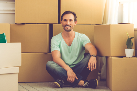 shifting: Handsome mature bearded man in casual clothes is sitting on the floor among boxes, looking at camera and smiling while moving to the new apartment
