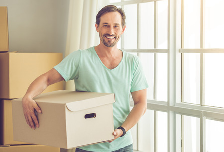 Handsome mature bearded man in casual clothes is carrying boxes, looking at camera and smiling while moving to the new apartment