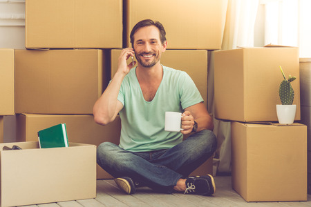 shifting: Handsome mature bearded man in casual clothes is sitting on the floor among boxes, talking on the mobile phone, looking at camera and smiling while moving to the new apartment