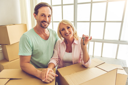 unpack: Beautiful mature couple in casual clothes is leaning on the boxes, looking at camera and smiling while moving to the new apartment. Woman is holding keys Stock Photo