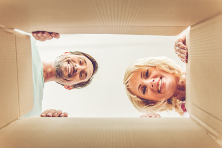 Bottom view of beautiful mature couple looking at camera and smiling while packing boxes for move