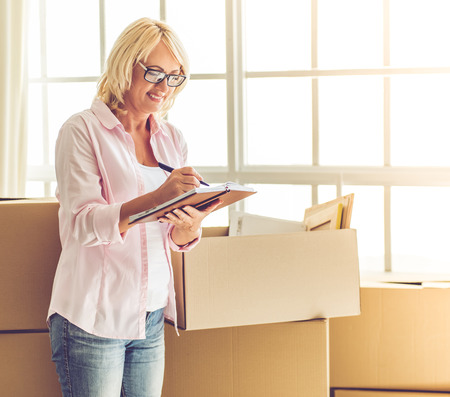 unpack: Beautiful mature woman in casual clothes and eyeglasses is packing her stuff into the boxes, making notes and smiling while moving to the new apartment