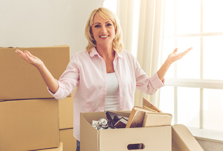 Beautiful mature woman in casual clothes is packing her stuff into the boxes, looking at camera and smiling while moving to the new apartment