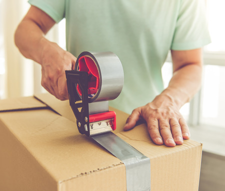 Freigestellte Bild von gut aussehend Mann in Casual Kleidung packen seine Sachen in die Boxen mit einem Klebeband beim Umzug in die neue Wohnung Standard-Bild - 63445866