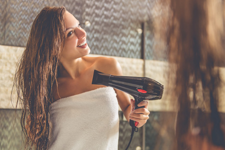 Beautiful young woman in bath towel is using a hair dryer and smiling while looking into the mirror in bathroom Фото со стока