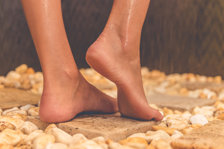stone wash: Beautiful feet of young woman standing on stones while taking shower in bathroom Stock Photo