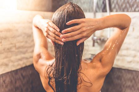 mujer bañandose: Vista trasera de la hermosa mujer joven que toma la ducha en el baño