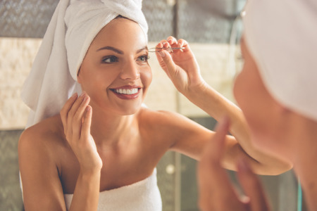 plucking: Beautiful young woman in bath towel is plucking eyebrows and smiling while looking into the mirror in bathroom Stock Photo