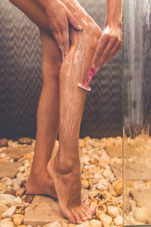 taking shower: Cropped image of beautiful young woman shaving her legs using a razor while taking shower in bathroom