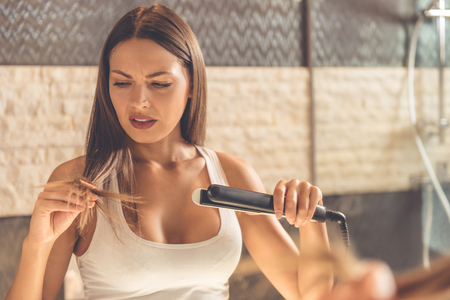 Beautiful young woman in white undershirt is looking at her damaged hair while using a hair straightener, standing in front of the mirror in the bathroom Imagens