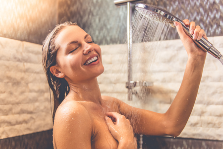 Beautiful young woman is smiling while taking shower in bathroom Stock Photo