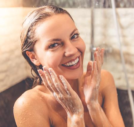 美しい若い女性はカメラを見て、浴室でシャワーを浴びながら笑みを浮かべて