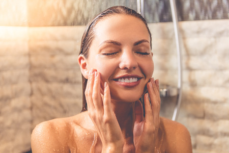 taking shower: Beautiful young woman is touching her face and smiling while taking shower in bathroom Stock Photo