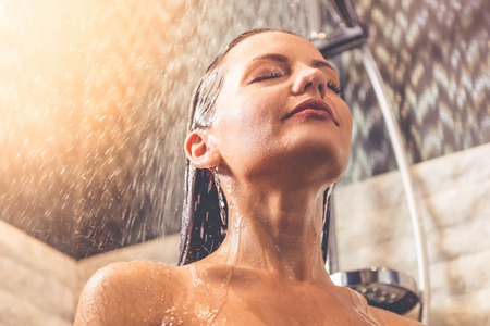 Low angle view of beautiful young woman smiling while taking shower in bathroom Stock Photo