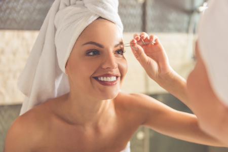 Beautiful young woman in bath towel is plucking eyebrows and smiling while looking into the mirror in bathroom Stock Photo