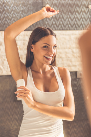 Beautiful young woman in white undershirt is using a deodorant and smiling while looking into the mirror in bathroom