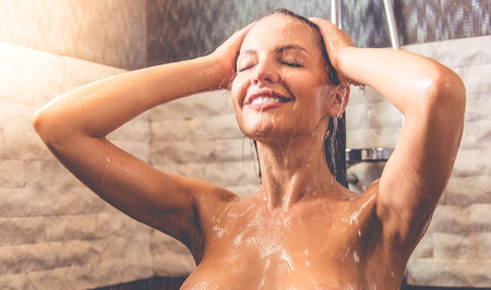 taking shower: Beautiful woman is smiling while taking shower in bathroom Stock Photo