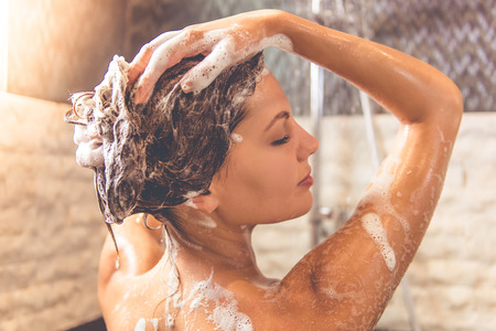 taking shower: Beautiful young woman is smiling and using shampoo while taking shower in bathroom