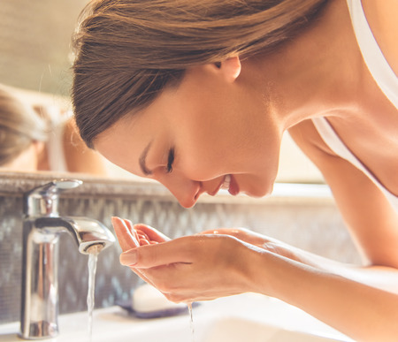 Beautiful young woman in white undershirt is washing her face and smiling while standing in front of the mirror in the bathroom Stock Photo