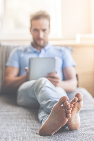 Handsome young man in casual clothes is using a digital tablet and smiling while resting on couch at home. Bare feet in focus