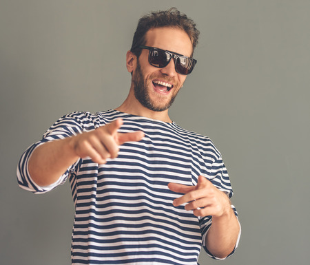 striped vest: Handsome stylish young man in sailors striped vest and sun glasses smiling, pointing and looking at camera, on gray background