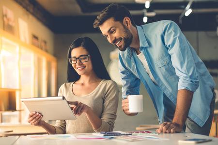 Schöne Paare von Designern in Freizeitkleidung ist mit einer digitalen Tablette, im Gespräch und lächelnd, während im Studio arbeiten Standard-Bild
