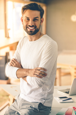 folded arms: Attractive designer in casual clothes is standing with folded arms, looking at camera and smiling while working in his studio