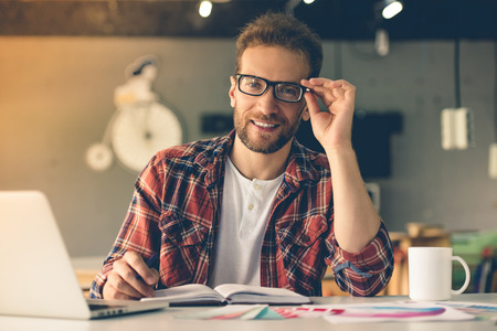 designer clothes: Handsome designer in casual clothes and eyeglasses is using laptop, making notes, looking at camera and smiling while working in his studio