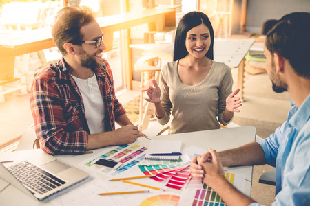 collegue: Group of beautiful designers in casual clothes is discussing affairs, choosing colors and smiling while working in studio Stock Photo