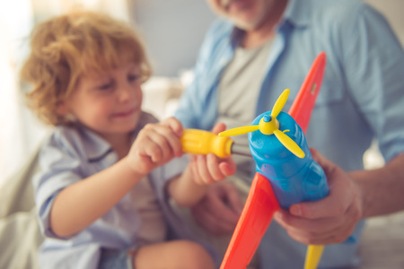 Cute little boy is playing with toys and his grandpa at home Stock Photo