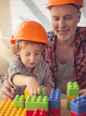 grand kid: Handsome grandpa and grandson in helmets are playing with construction set and smiling while sitting on couch at home