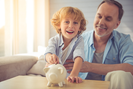 grand kid: Cute little boy is putting coin into the piggy bank, looking at camera and smiling while spending time with his grandpa at home