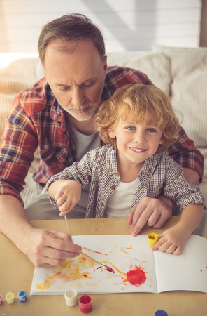 grand kid: Handsome grandpa and grandson are painting using gouache and smiling while spending time together at home